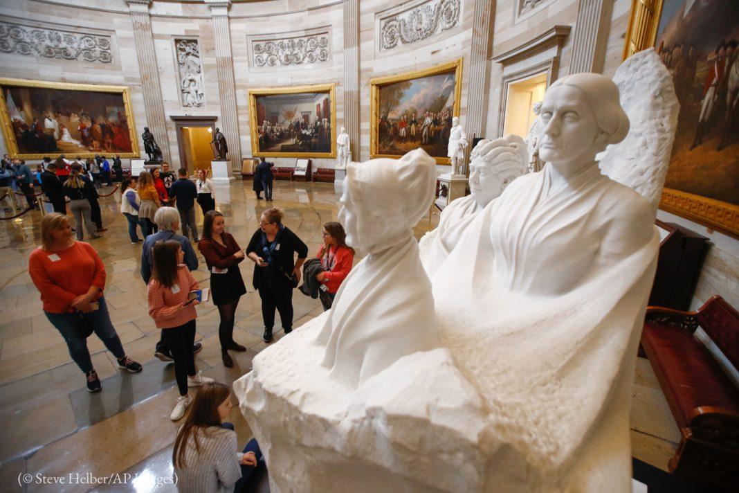 People in a room looking at a sculpture (© Steve Helber/AP Images)