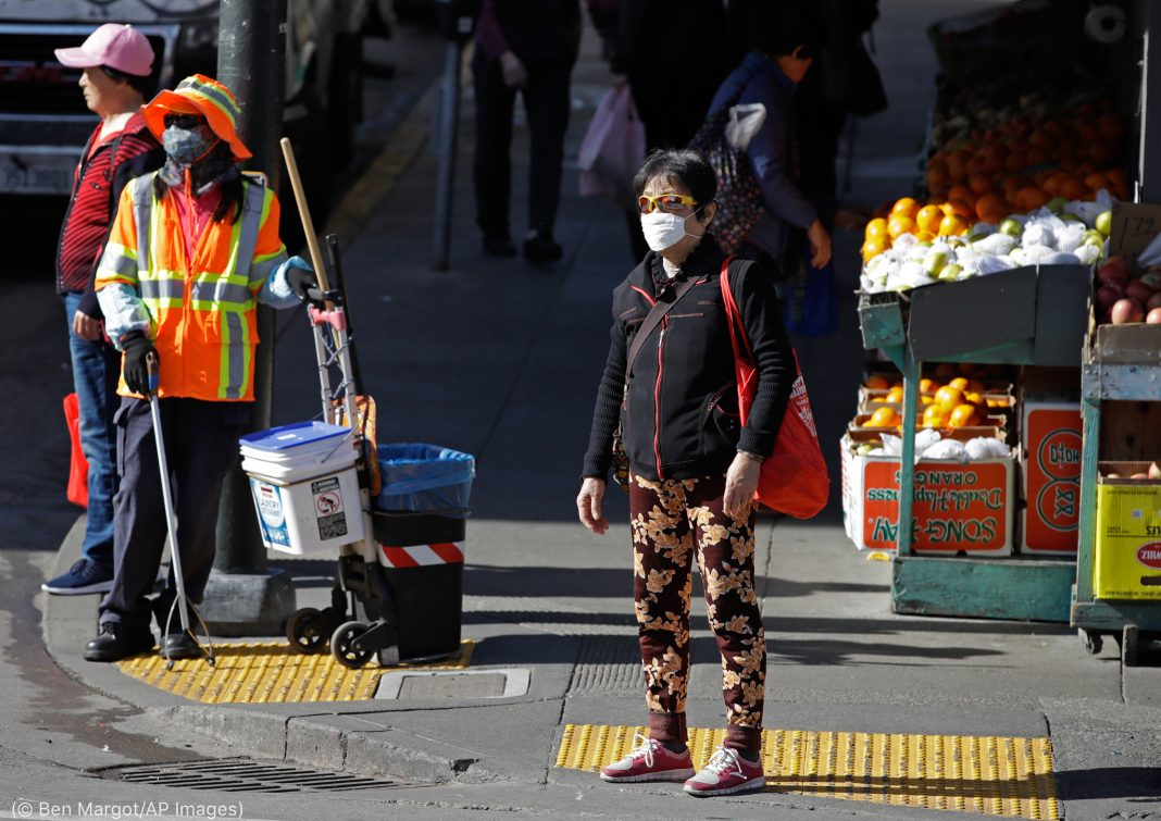 People standing on a city street corner wearing masks (© Ben Margot/AP Images)