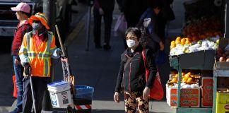 Orang-orang berdiri di sudut jalan kota memakai masker (© Ben Margot/AP Images)