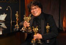 Pria memegang banyak piala Oscar (© Richard Shotwell/Invision/AP Images)