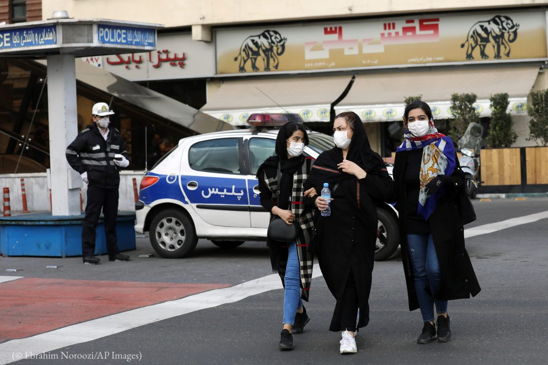 A policeman and pedestrians wearing masks to help guard against the Coronavirus walk on Tehran street (©