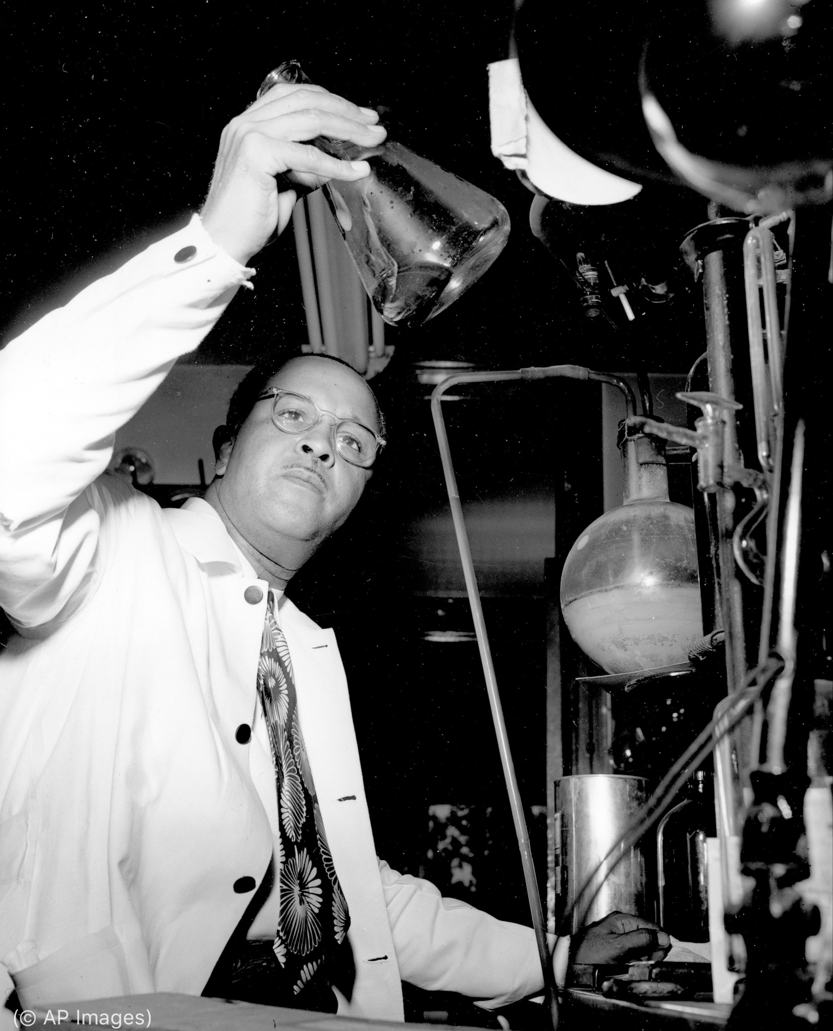 Percy L. Julian holding up and examining glass container (© AP Images)