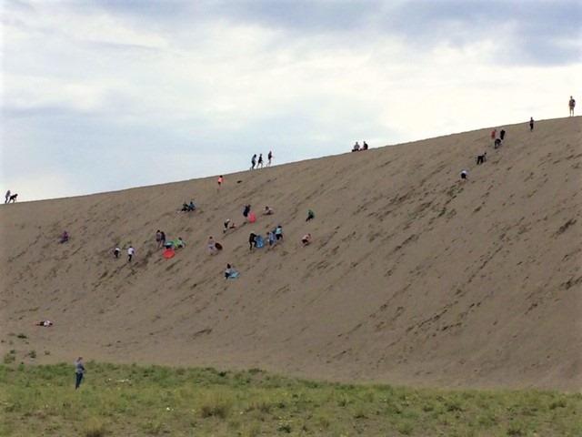 走上最高的沙丘费时费力,一些人就近爬上较低的沙丘,然后滑沙而下。这是今年独立日长假期间,人们在公园里滑沙的景象。