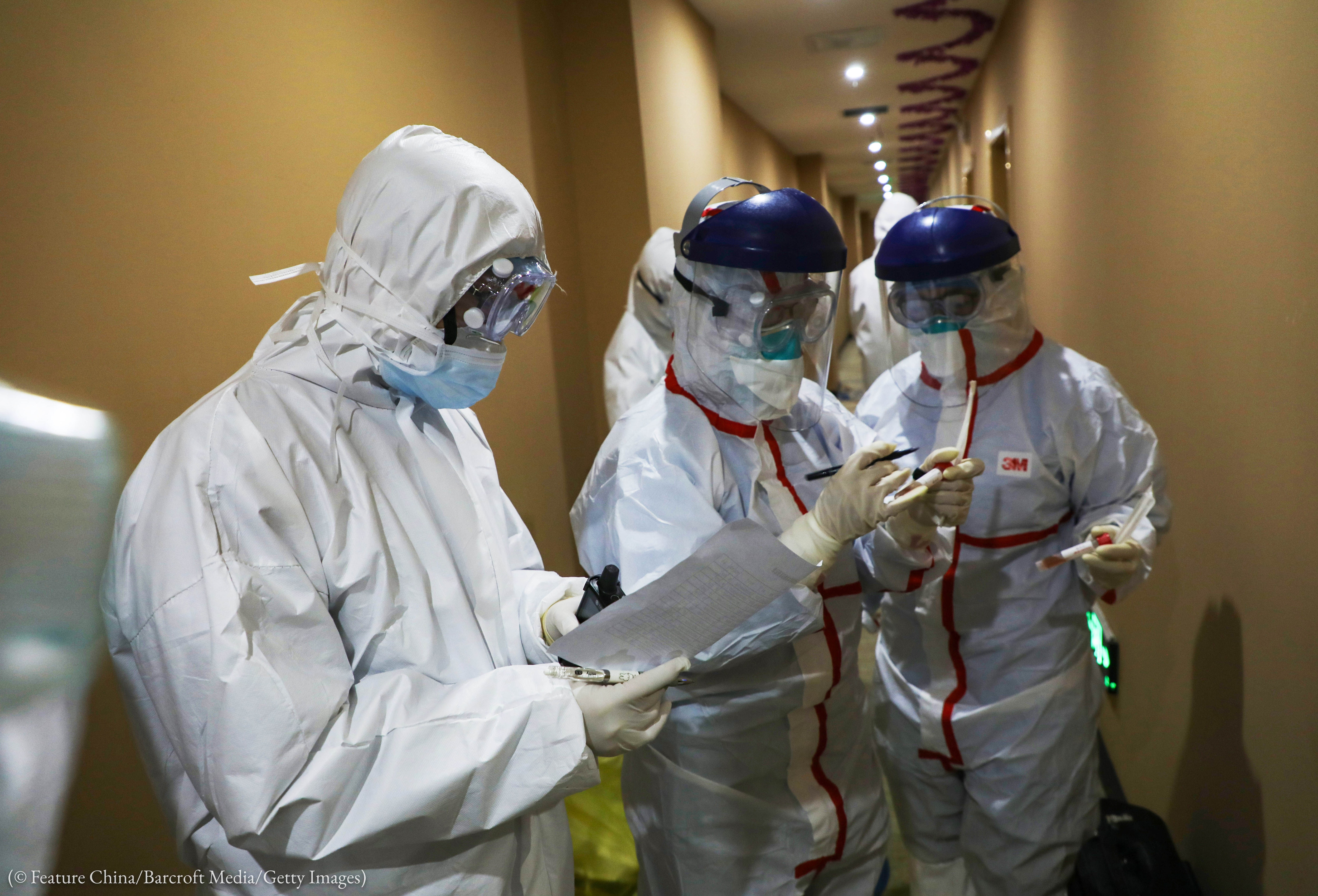 Health workers in protective garb taking notes in a hallway (© Feature China/Barcroft Media/Getty Images)