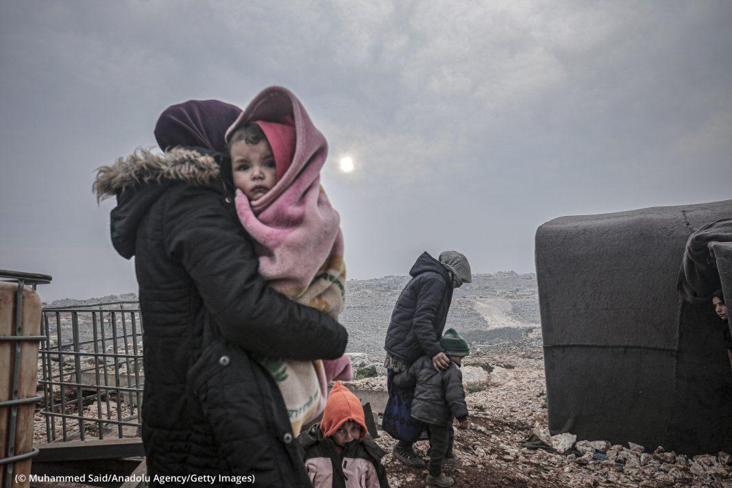 Adulto carregando criança e outras pessoas próximas (© Muhammed Said/Anadolu Agency/Getty Images)