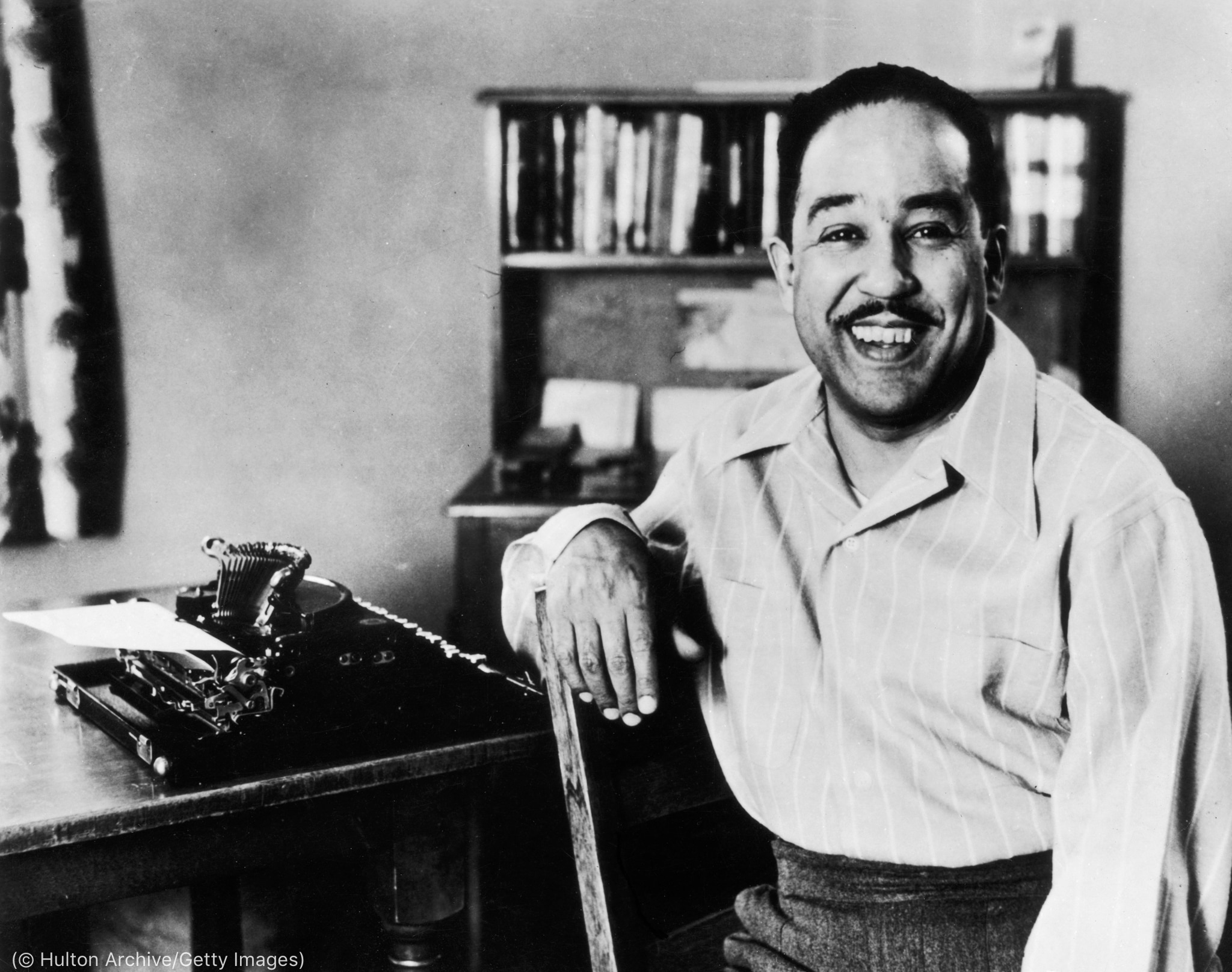 Langston Hughes sitting next to typewriter on desk (© Hulton Archive/Getty Images)