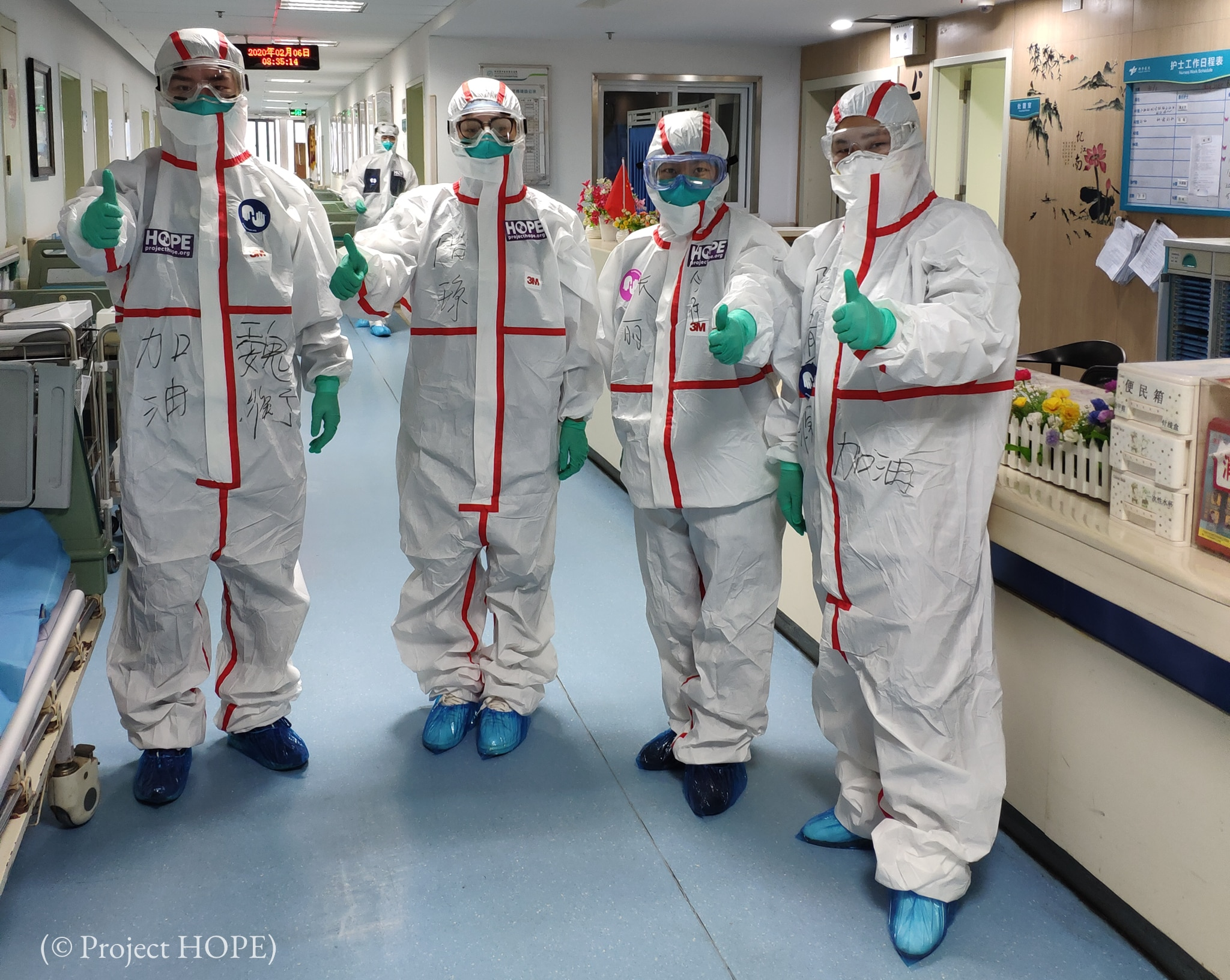Four people in protective suits giving thumbs-up sign (© Project HOPE)