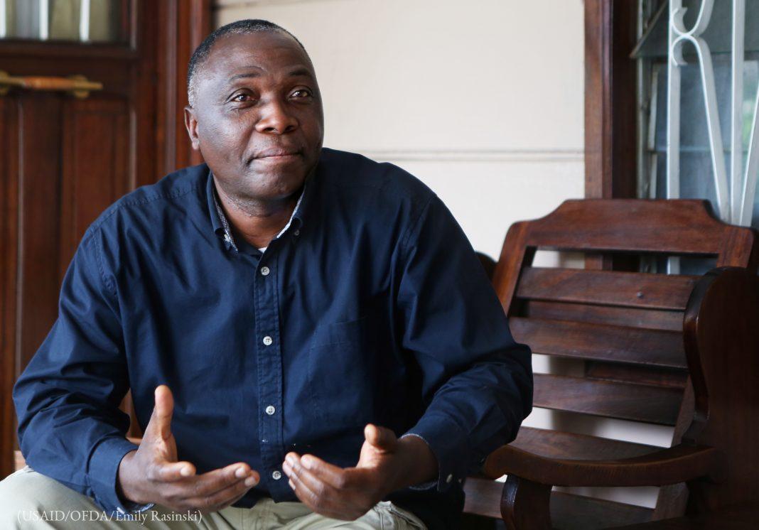 El obispo Bernard Kabamba sentado y hablando (USAID/OFDA/Emily Rasinski)
