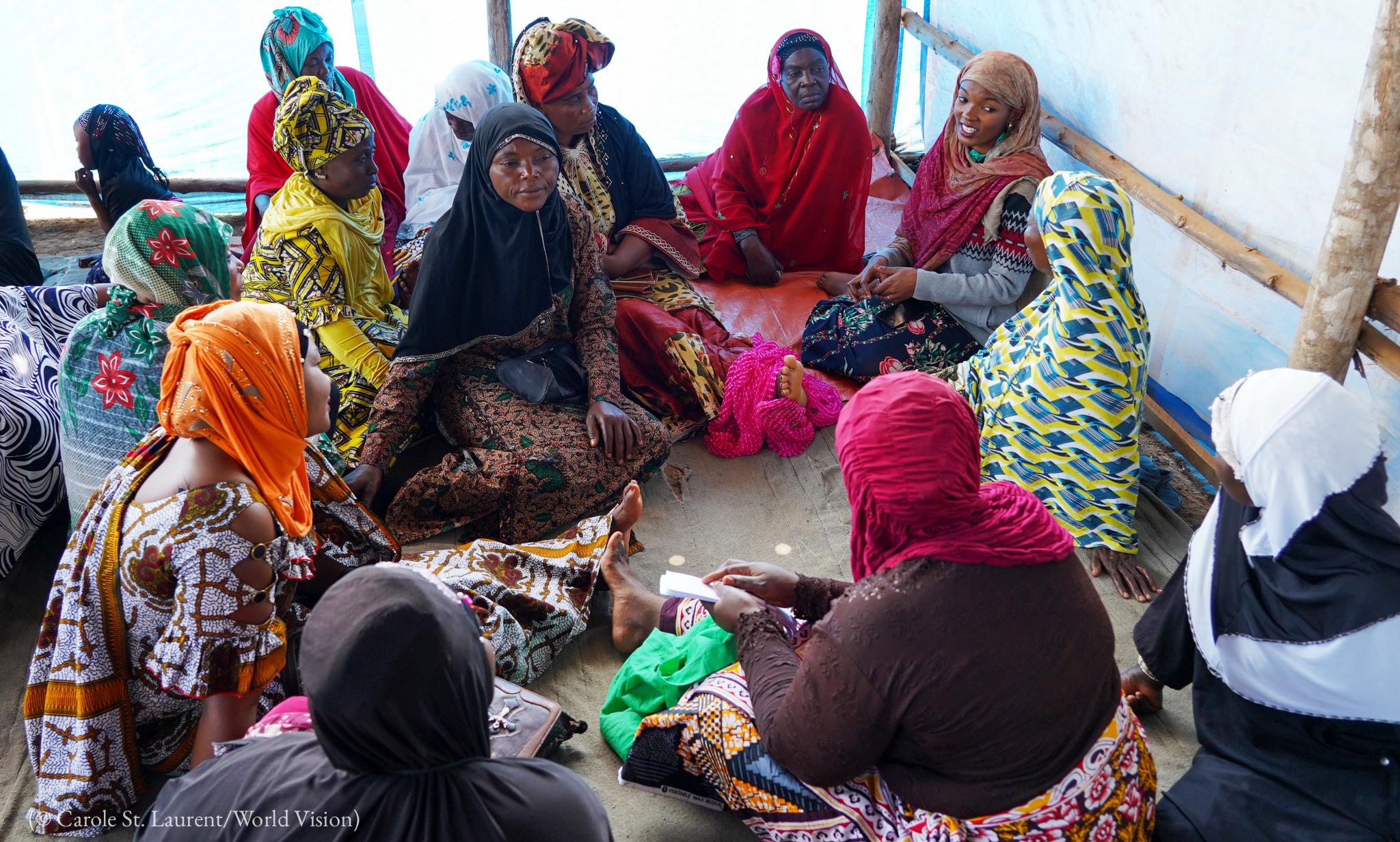 Mujeres con ropas de colores y pañuelos en la cabeza sentadas en círculo en el piso (© Carole St. Laurent/World Vision)