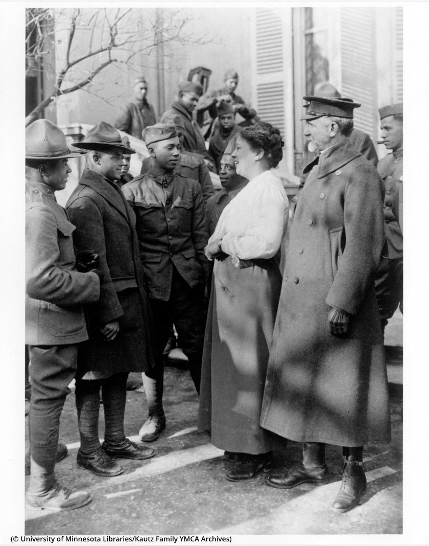 Sekelompok tentara berbicara dengan seorang perempuan (© University of Minnesota Libraries, Kautz Family YMCA Archives)