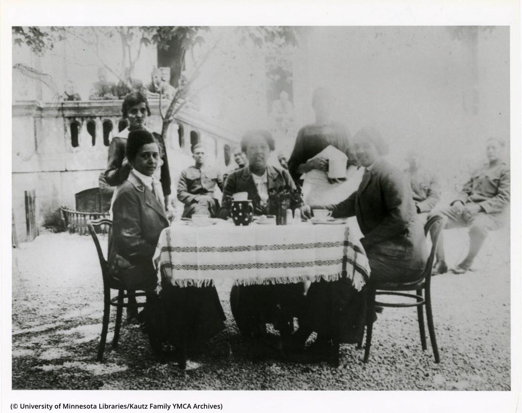Foto pudar orang-orang yang duduk dan berdiri mengelilingi meja di luar ruangan (© University of Minnesota Libraries, Kautz Family YMCA Archives)