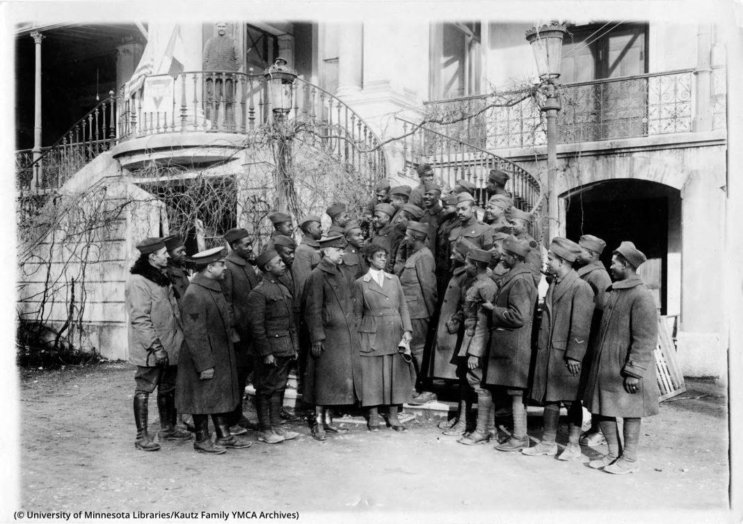 Sekelompok besar tentara berfoto bersama seorang perempuan (© University of Minnesota Libraries, Kautz Family YMCA Archives)
