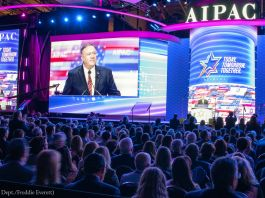 Pompeo speaking to a crowd, with his image on a screen behind him (State Dept./Freddie Everett)