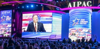 Mike Pompeo speaking to a crowd with his image on a screen behind him (State Dept./Freddie Everett)