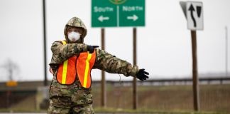 Soldier with mask directing traffic (U.S. Army National Guard/Specialist Michael Schwenk)