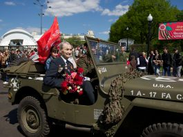 Man holding flowers and sitting in military jeep (© Alexander Zemlianichenko Jr/AP Images)