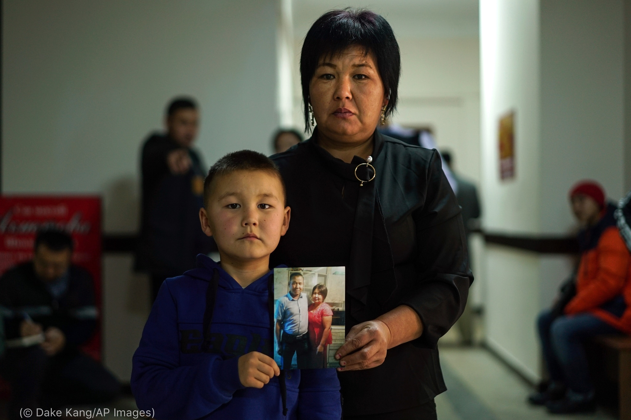 Child and woman standing facing the camera and holding a photo of two people (© Dake Kang/AP Images)