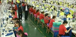 Overhead view of rows of people sitting at tables working (© CCTV/AP Video) )