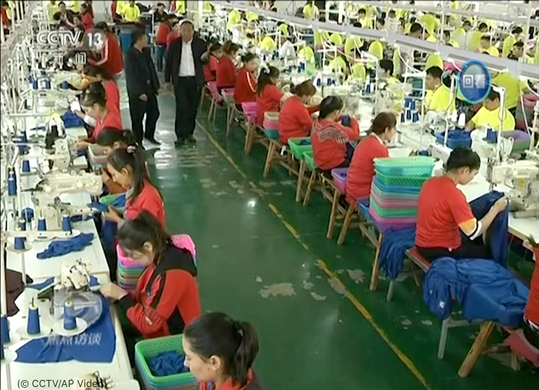 Overhead view of rows of people sitting at tables working (© CCTV/AP Video)