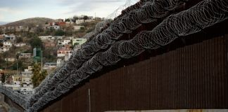 Железная стена, покрытая колючей проволокой, со зданиями на заднем плане (© Charlie Riedel/AP Images)