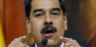 Nicolás Maduro talking into microphone and pointing with both hands (© Ariana Cubillos/AP Images)