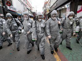 Orang-orang berjajar berpakaian pelindung menyemprot jalanan kota (© Ahn Young-joon/AP Images)
