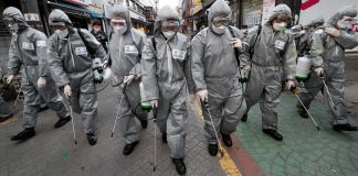 Line of people wearing protective suits spraying city street (© Ahn Young-joon/AP Images)