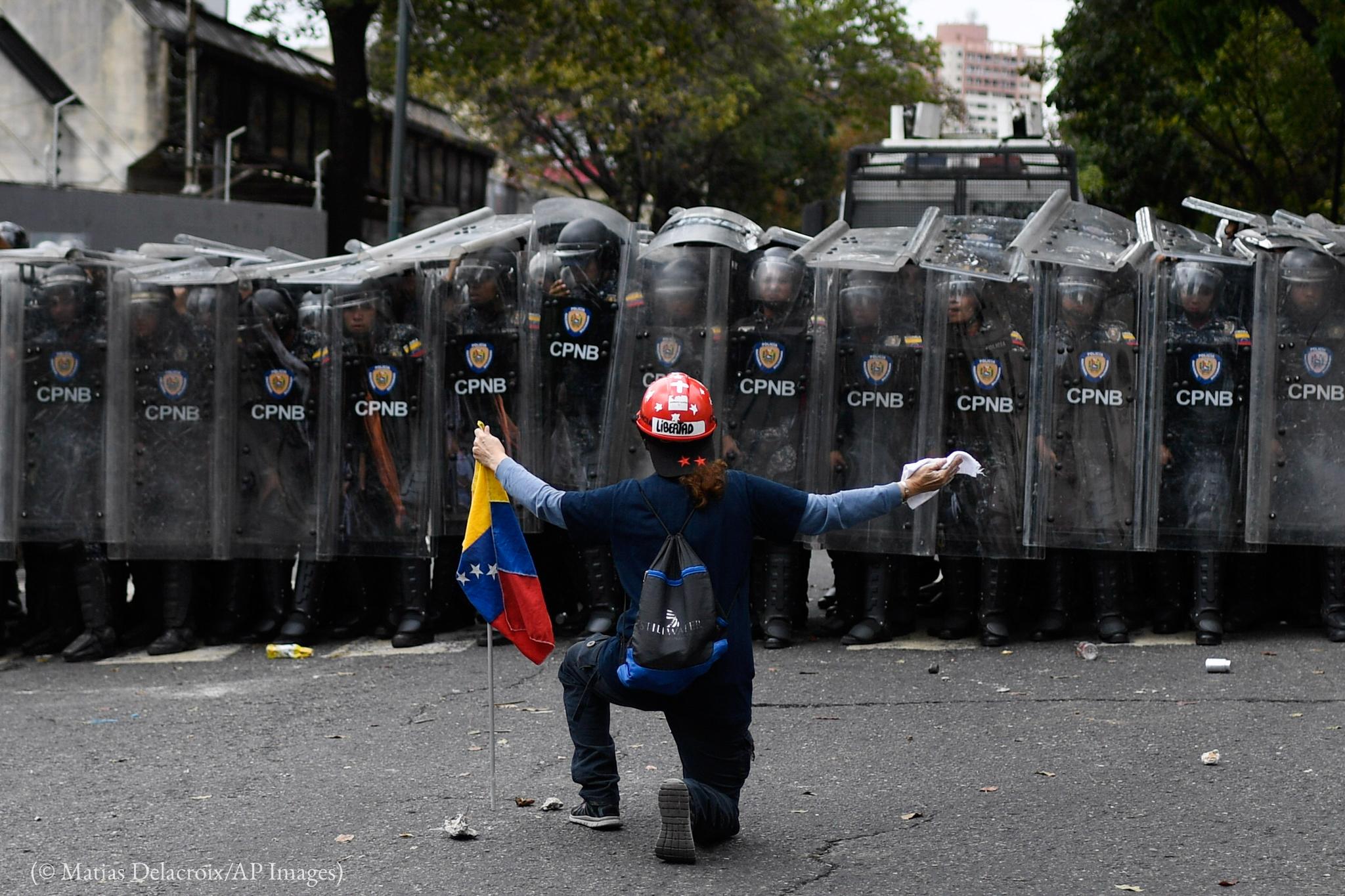 Homem ajoelhado na frente de fileira de policiais com escudos (© Matias Delacroix/AP Images)
