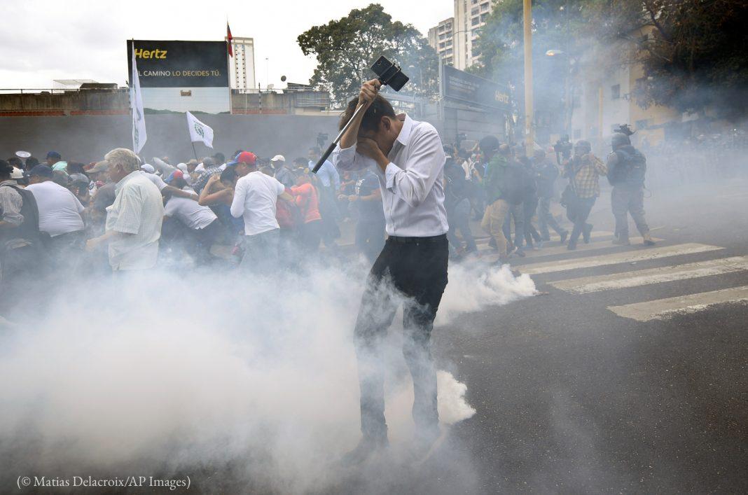 Homem cobre o rosto para não inalar gás lacrimogêneo (© Matias Delacroix/AP Images)