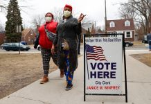 """ماسک پہنے ہوئے عورتیں """"یہاں ووٹ دیں"""" کے سائن کے قریب سے گزر رہی ہیں۔ (© Paul Sancya/AP Images)"""