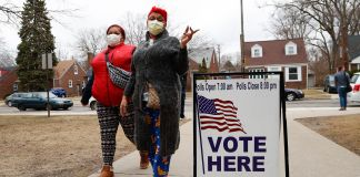 "Women with masks walking next to ""vote here"" sign (© Paul Sancya/AP Images)"
