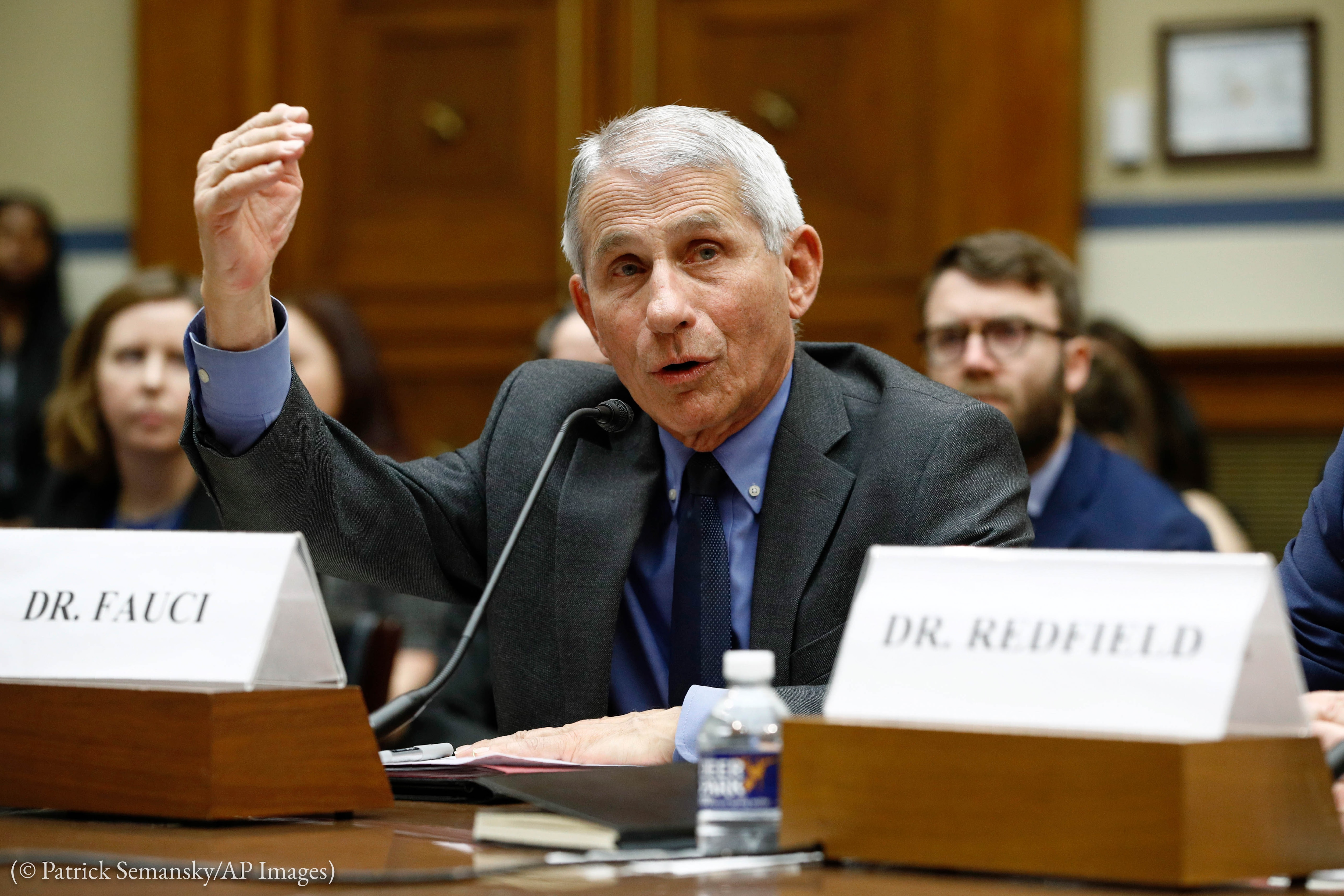 Anthony Fauci with arm raised sitting at table (© Patrick Semansky/AP Images)