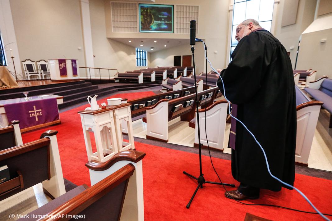 Pendeta menyiapkan kamera menghadap gereja kosong (© Mark Humphrey/AP Images)