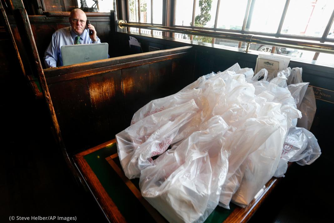 Seorang pria duduk di restoran berbicara di ponsel dengan banyak tas berisi makanan pesanan siap ambil berjajar di atas meja di depannya (© Steve Helber/AP Images)