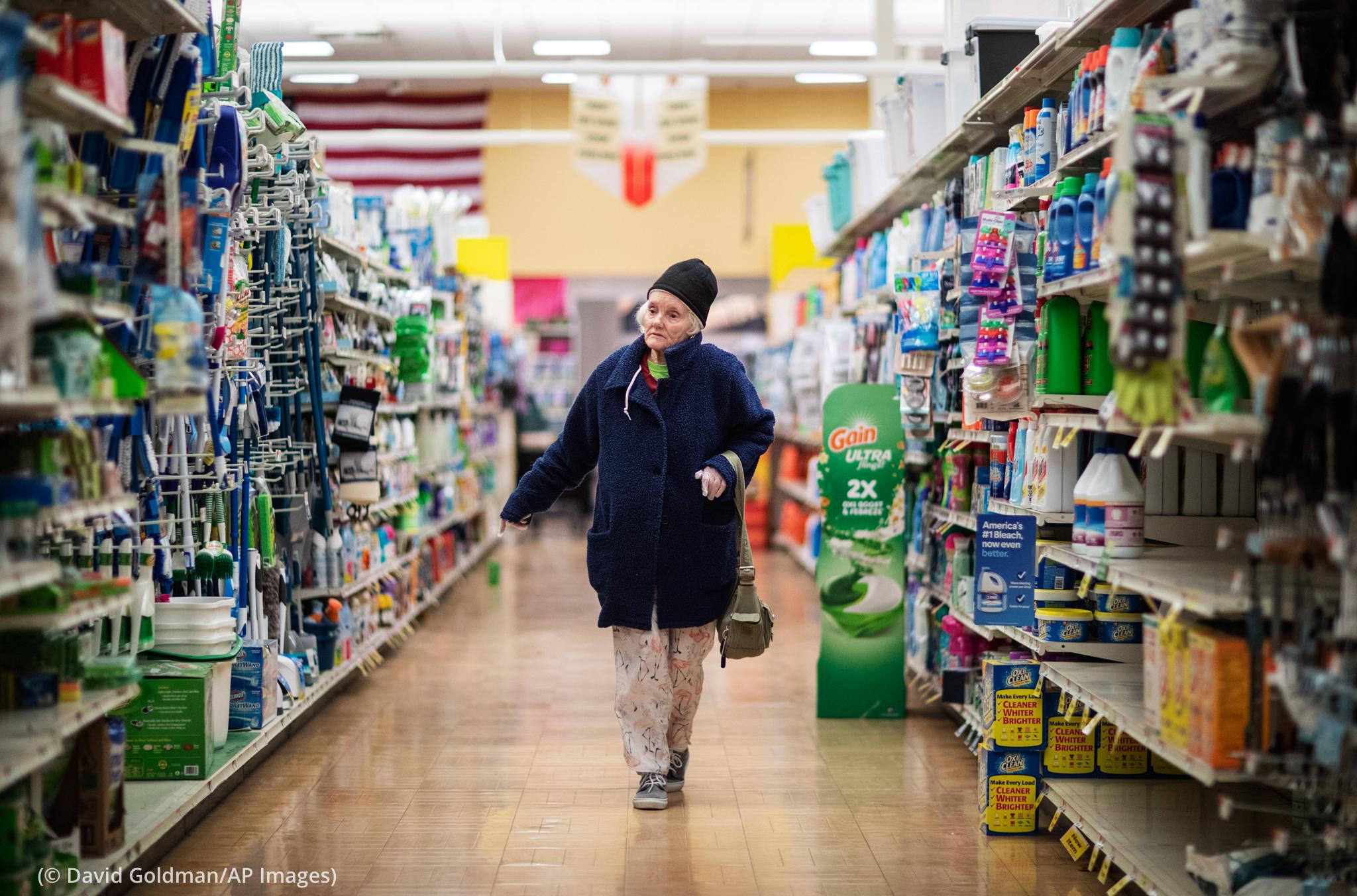 Person walking down a grocery store aisle (© David Goldman/AP Images)