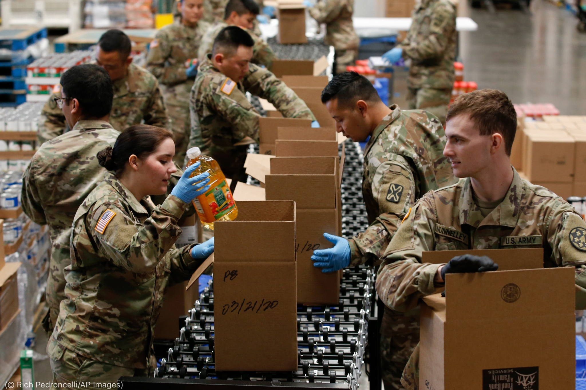 Soldiers putting food in boxes (© Rich Pedroncelli/AP Images)