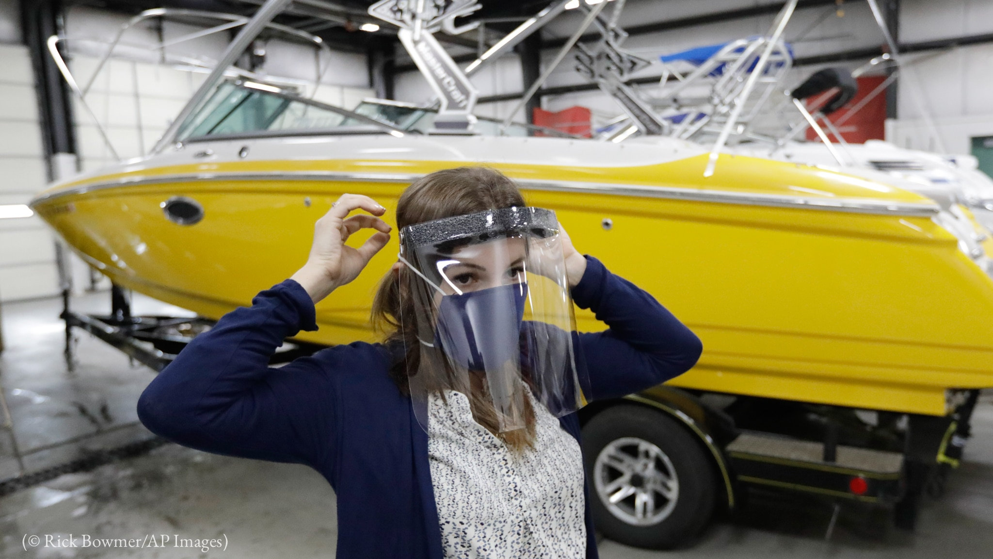Woman standing in front of a boat while wearing a face mask and face shield (© Rick Bowmer/AP Images)