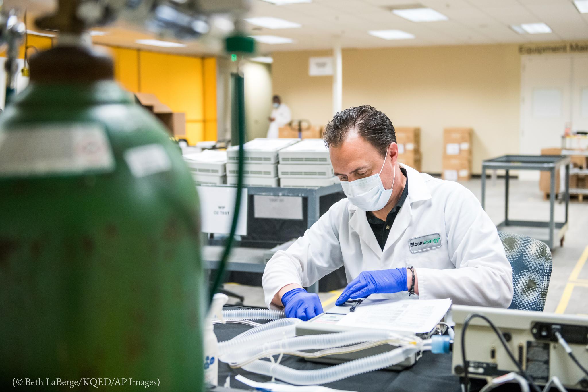 Hombre con bata de laboratorio, mascarilla facial y guantes que trabaja en un ventilador (© Beth LaBerge/KQED AP Images)