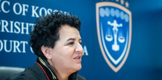 Afërdita Bytyqi sentada, y al fondo palabras y un emblema (USAID/Sebastian Lindstrom)