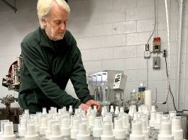 Man standing beside table of bottles (© Litchfield Distillery)
