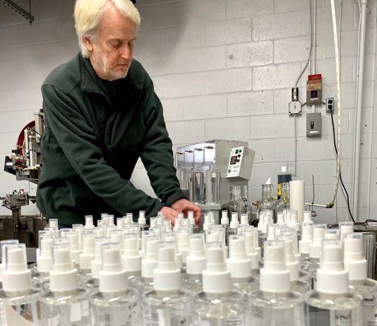 میز پر پڑی بوتلوں کے پاس ایک آدمی کھڑا ہے۔ (© Litchfield Distillery)
