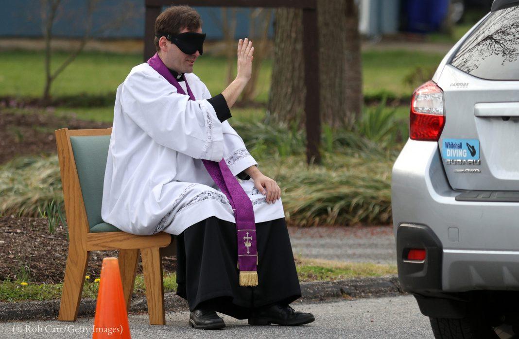 Sacerdote católico con los ojos vendados sentado en una silla fuera da la absolución al conductor de un auto (© Rob Carr/Getty Images)