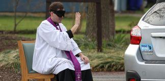 Pastor Katolik dengan mata tertutup duduk di bangku di luar ruangan dan membuat tanda salib untuk pengemudi di mobil (© Rob Carr/Getty Images)