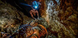 سر پر بندھے ہوئے لیمپ کے ساتھ ایک آدمی سونے کی کان میں کام کر رہا ہے۔ (© Juan Barreto/AFP/Getty Images)