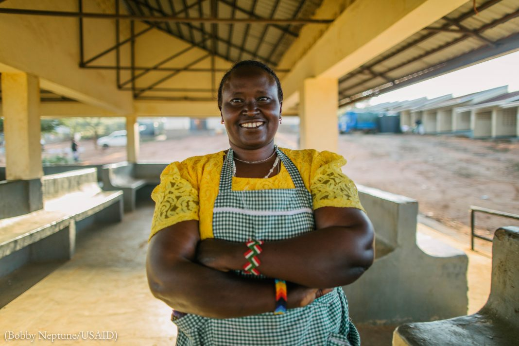 Smiling woman standing with arms folded in open-sided building (Bobby Neptune/USAID)