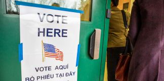 """ایک دروازے پر مختلف زبانوں میں """"یہاں ووٹ دیں"""" کا سائن۔ (State Dept./D.A. Peterson)"""