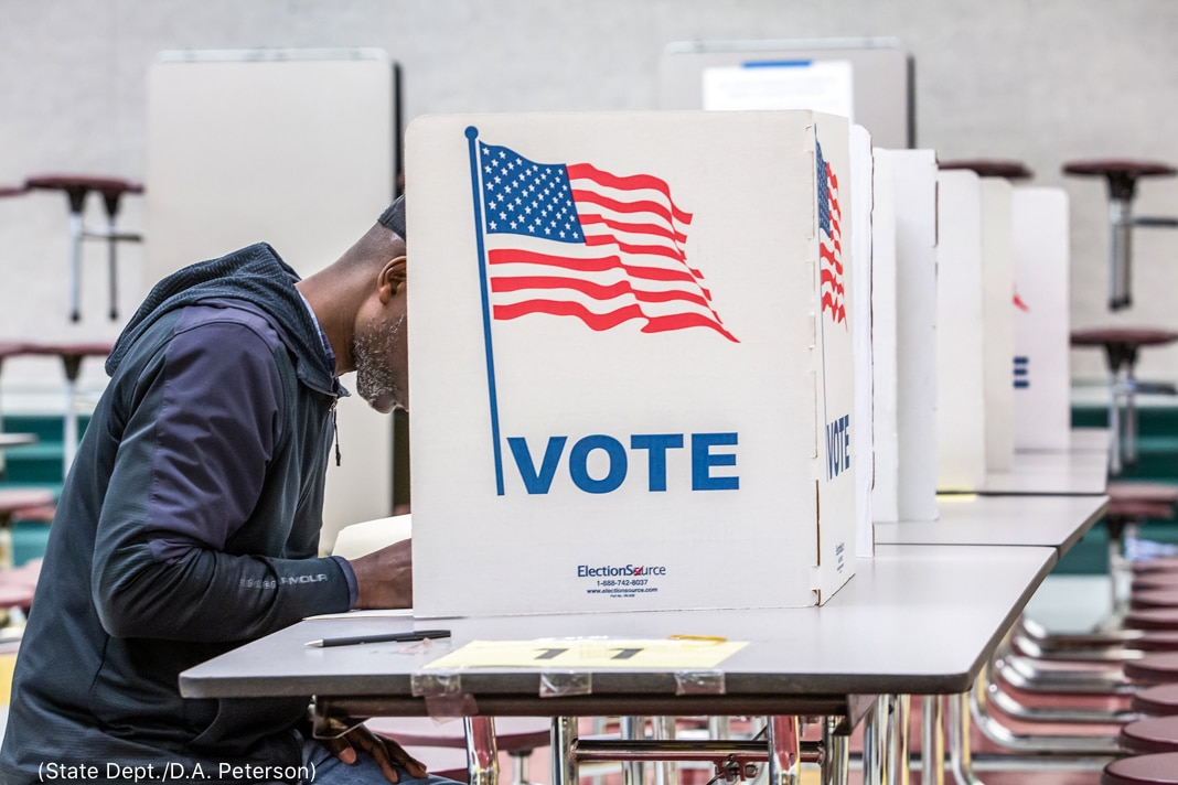 Un homme noir assis à une table, à demi dissimulé derrière un panneau en carton, en train de voter (Département d'État/D.A. Peterson)