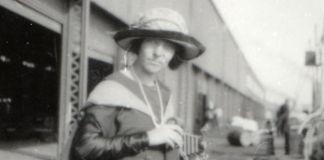 Photo estompée, en noir et blanc, d'une femme se tenant à l'extérieur d'une grande installation (© Lowell Observatory Archives)