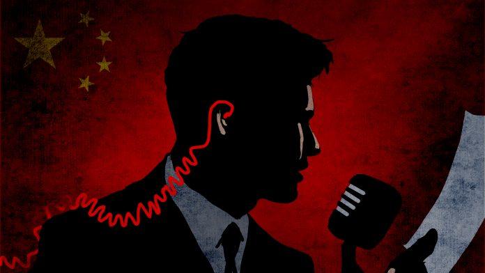 کانوں میں لگے سماعتی آلے، کاغذ ہاتھ میں پکڑے اور مائیکروفون میں بولتے ہوئے ایک آدمی کا تصویری خاکہ۔ (State Dept./D. Thompson)