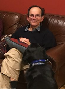 Daniel Becker sitting on a couch, black dog watching him (© Madaline B. Harrison)